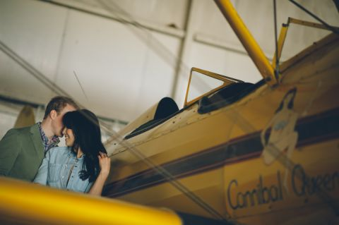 Couple poses against a biplane during their engagement session at an airfield in Philadelphia, PA. Captured by NJ wedding photographer Ben Lau.