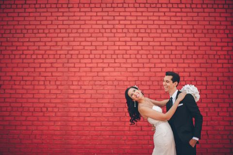 Couple poses by a painted red brick wall in Red Hook, Brooklyn. Captured by NYC wedding photographer Ben Lau.