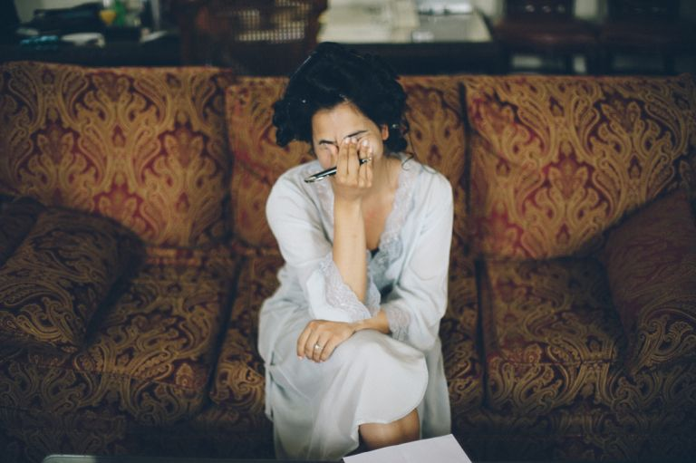 Bride covers her face before writing her letter to the groom at the Castle on the Hudson in Tarrytown, NY. Captured by NYC wedding photographer Ben Lau.