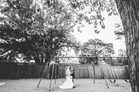Bride and groom pose on a swing set in Clarendon, VA. Captured by NYC wedding photographer Ben Lau.