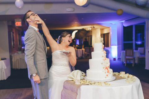 Bride smushes cake into the groom's face at their wedding at McLoone's Pier House in Long Branch, NJ. Captured by NYC wedding photographer Ben Lau.