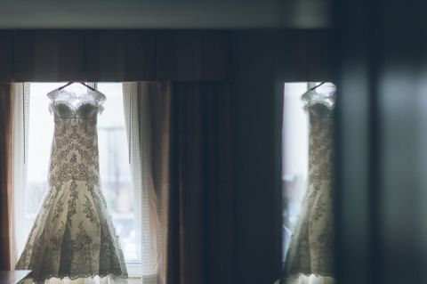 Wedding dress hanging on the window. Crest Hollow Country Club wedding captured by NYC wedding photographer Ben Lau.