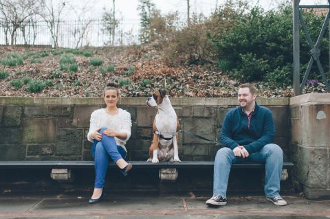 Couple sits on a bench with their dog during their engagement session in Central Park. Captured by NYC wedding photographer Ben Lau.