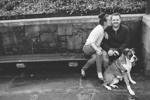 Girl kisses guy while sitting on a bench with their dog, during their engagement session in Central Park. Captured by NYC wedding photographer Ben Lau.