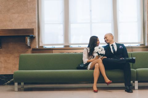 Jen and Edwin wait on the couch at the marriage bureau in NYC. Captured by NYC City Hall wedding photographer Ben Lau.