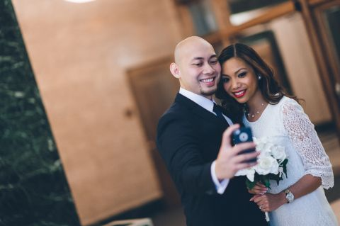 Jen and Edwin take a selfie at the marriage bureau in NYC. Captured by NYC City Hall wedding photographer Ben Lau.