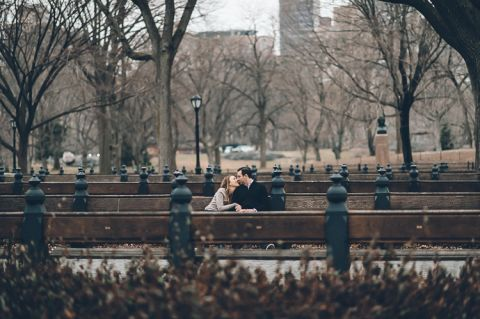 Couple sits on empty benches, during their engagement session in Central Park, with NYC wedding photographer Ben Lau.