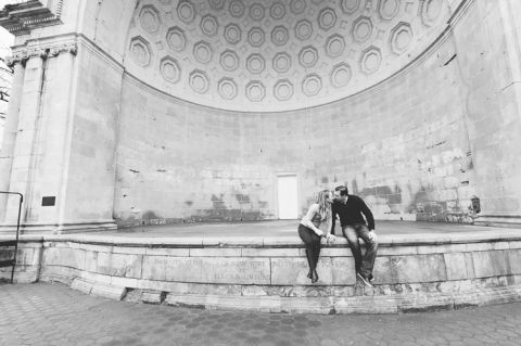 Couple sits together on an empty stage, during their engagement session in Central Park, with NYC wedding photographer Ben Lau.