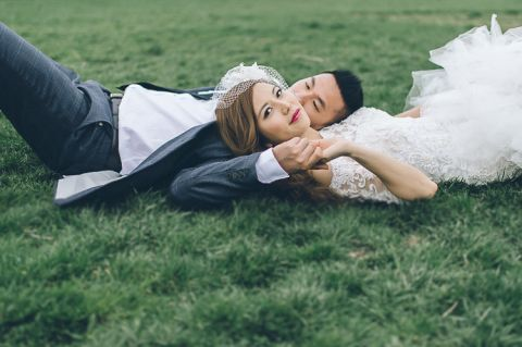 Couple lies on the grass during their wedding photo session with NYC wedding photographer Ben Lau.