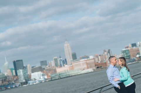 NYC skyline behind the couple during their engagement session in Hoboken, NJ. Captured by NJ wedding photographer Ben Lau.