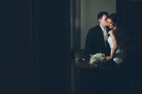 Groom kisses bride in the shadows during their wedding photo session at The Palace at Somerset Park. Captured by awesome NJ wedding photographer Ben Lau.
