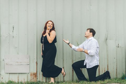 Yuriy serenades Alina with flowers during their engagement session in Baltimore with NJ wedding photographer Ben Lau.