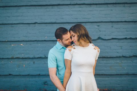 Couple poses in front of a blue wall during their fun engagement session in NYC. Captured by NYC wedding photographer Ben Lau.