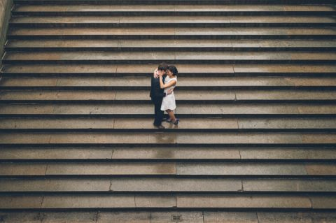 Couple share a kiss on the steps during their engagement session in Central Park. Captured by NYC wedding photographer Ben Lau.
